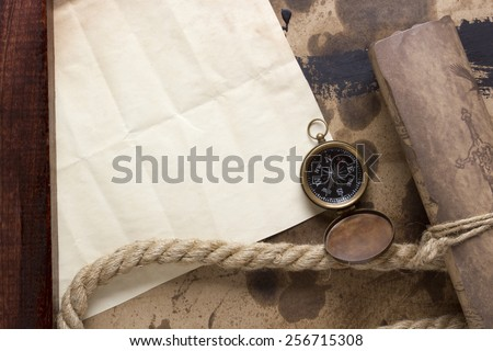 Roll of parchment with a compass and marine rope.