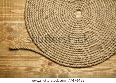 Roll of rough rope on wooden background