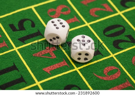 roll of the white dice on  game table in a casino