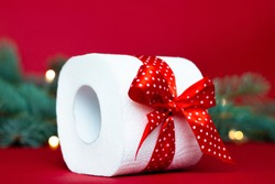 Roll of toilet paper as a christmas gift near a branch of a christmas tree on a red background