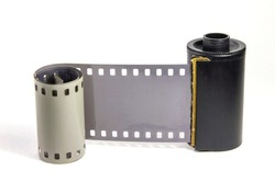 Roll of undeveloped 35 mm, black and white negative photographic film on a white background