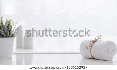 Roll of white spa towel tied with hemp rope on white counter table, copy space.