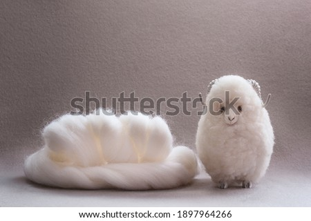 Roll of white wool for handcraft, merino wool, handmade toy made of wool. Suitable for knitting, wool felting. Stock photo ©
