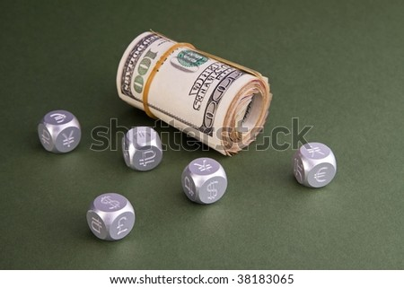 Roll U.S. money and aluminum dice with world currency symbols.  Conceptual image for world finance, money markets, banking, investing, etc.  On a green, lightly textured paper background.