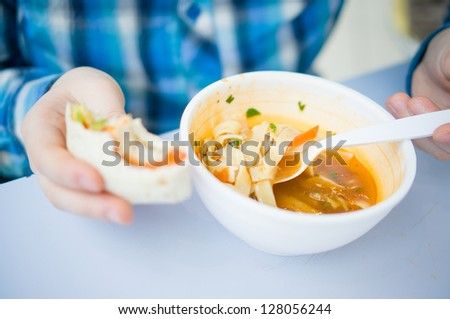 Roll with chicken and vegetables and plate of soup with noodles in fast food restaurant