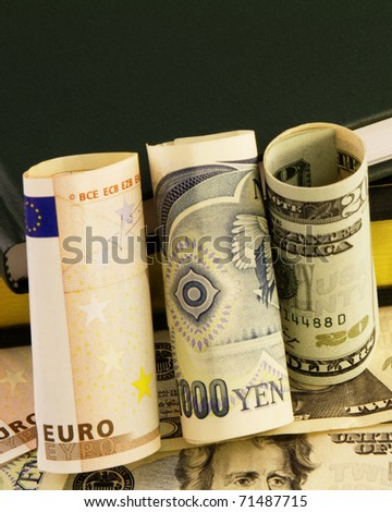 Rolled  bills of euro, yen, and dollars is placed against ledgers and currency to depict global financial issues.
