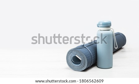 Rolled blue yoga mat and blue water bottle on grey wooden surface. Gender neutral fitness yoga and exercise concept with copy space. Active lifestyle. Workout at home or gym banner ストックフォト ©