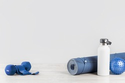 Rolled blue yoga mat and white metal water bottle flask grey wooden surface Dumbbell rubber resistance band. Gender neutral fitness and exercise concept and hydration with copy space. Active lifestyle