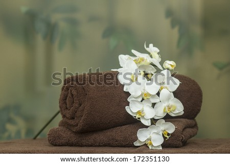 Rolled brown towel with flowers