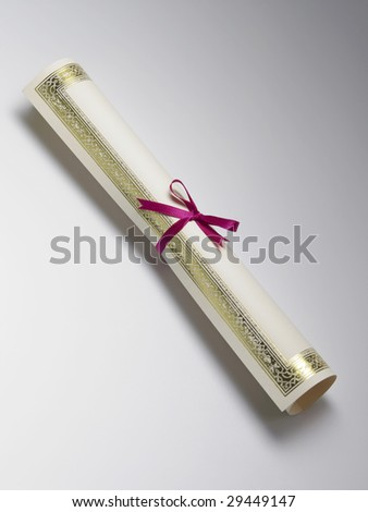 rolled certificate with red ribbon on the plain background