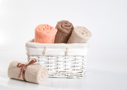 Rolled coral, beige and brown terry towels on a white background, rolled different colors terry towels with a ribbon against a white backdrop, towels in a white basket in front of a white  backdrop