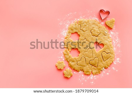 Rolled dough with rolling pin. Heart shaped cookie cutting out. Top view Stock photo ©
