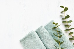 Rolled fluffy green towels and green eucalyptus branch on white background. Minimalist scandinavian style. Hygiene, wellness well-being, body care concept. Copy space, flat lay