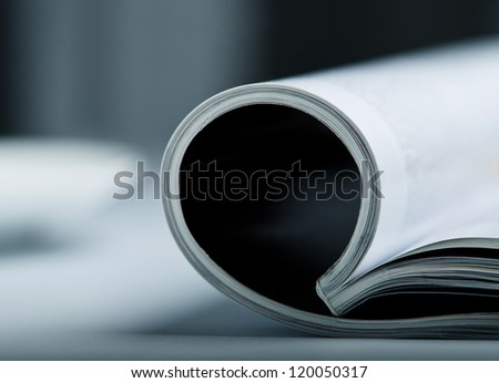Rolled glossy magazine on a table with very shallow depth of field.