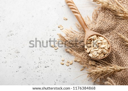 Rolled oats and ears of wheat on concrete background with copy space for text #1176384868