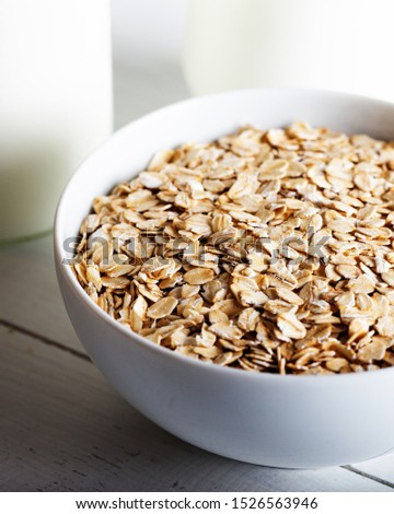 Rolled oats or oat flakes in bowl with bottle of milk on white background. #1526563946