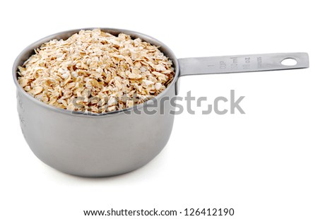 Rolled oats presented in an American metal cup measure, isolated on a white background