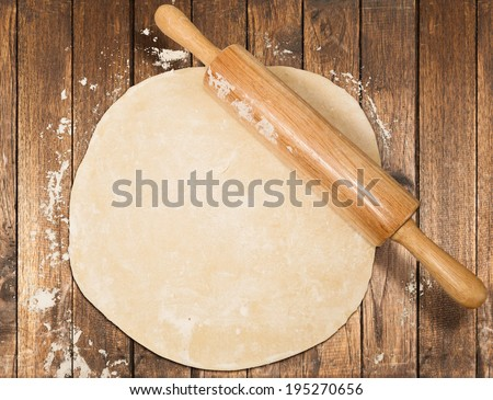 Rolled out dough on table with rolling pin