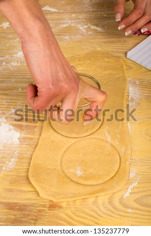 Rolled out piece of dough being cut out to make baglels