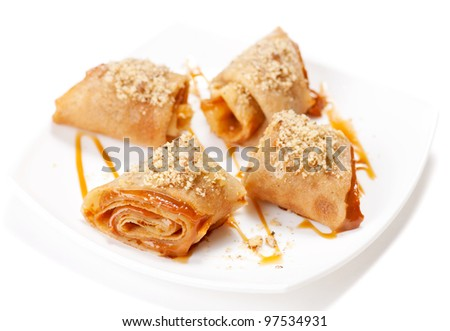 Rolled pancakes with caramel mousse and nuts. On white