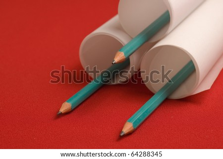 Rolled papers and three pencils