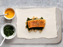 Rolled pastry dough, salmon fillet, spinach and fried mushrooms layered. Preparing ingredients before baking. Step by step cooking process. Salmon Wellington with spinach and champignons.