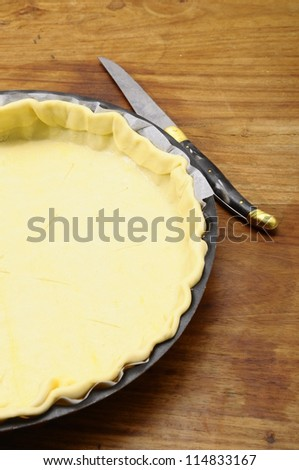 Rolled pastry sheet in pie dish and knif