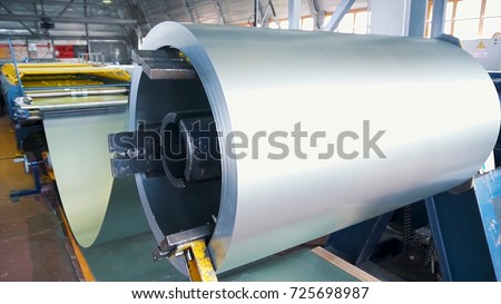 Rolled steel. Stack of rolls, Cold rolled steel coils in action. Galvanized Steel Sheet and rusty rim. Cold rolled steel coils. he drum turns the metal sheets in the production. Industrial