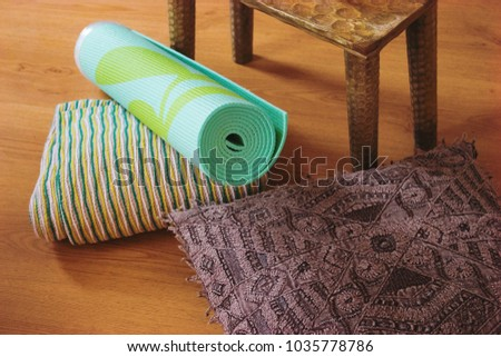 Rolled up aqua or teal yoga mat with pattern. Detail of yoga pad for studio or home practice. Still life of meditation accessories for relaxation or peace of mind. Zen candles, pillows and blanket, #1035778786