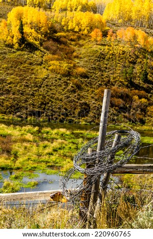 Rolled up barb wire fencing hanging on fence post in colorful mountain meadow