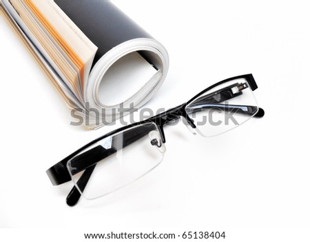 Rolled up black colored magazine and glasses over white background