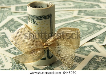 Rolled up dollar bills with a golden bow  on a dollar bill background, room for text