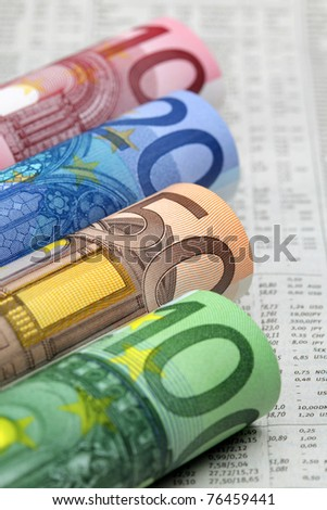 Rolled up Euro bills on financial newspaper
