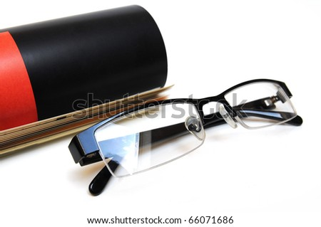 Rolled up magazine and black colored glasses over white background