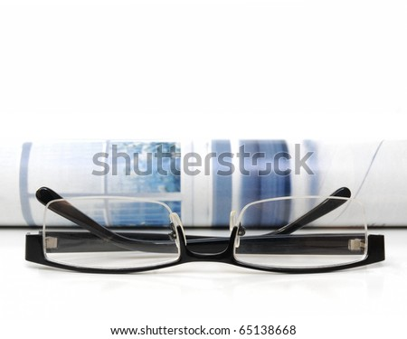 Rolled up magazine and glasses over white background