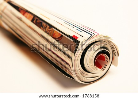 Rolled up magazine isolated on white - stock photo