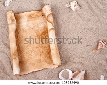 Rolled up old and weathered blank paper in the sand