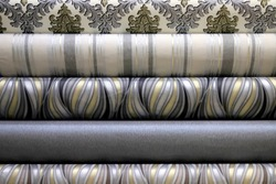 Rolled up rolls of vinyl wallpaper in a building supermarket, shop. Gray, white, beige wallpaper for the wall, decorative finishing materials for the renovation of a room, interior