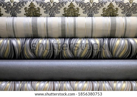 Rolled up rolls of vinyl wallpaper in a building supermarket, shop. Gray, white, beige wallpaper for the wall, decorative finishing materials for the renovation of a room, interior Stockfoto ©