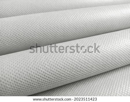 rolled white polypropylene fabric. non-woven fabric background with fibrous texture. industrial bag material Stockfoto ©