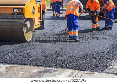 Roller and workers on asphalting and repair of city streets stock photo