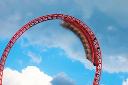 Roller coaster ride filled with thrill seekers doing loop, cloudy sky background. Roller coaster. Wagon in motion