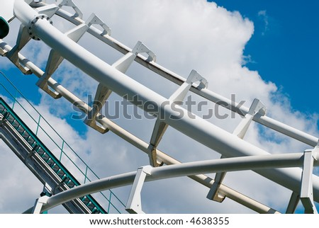 roller-coaster tracks at the cloudy blue sky