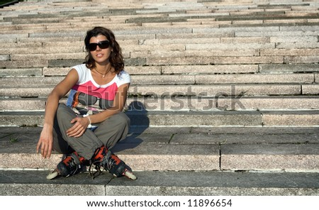 Roller girl sitting at stairs at sunny day. - stock photo