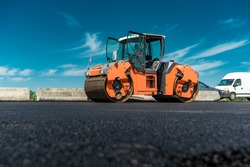 Roller rolling fresh hot asphalt on the new road. Road construction.