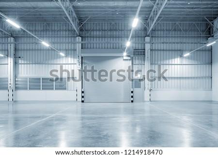 Roller shutter door and concrete floor inside factory building for industry background.