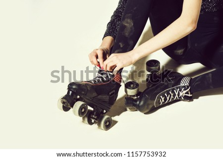 roller skates on woman or girl in black tie shoe laces with hand, has red manicure, rest and sit isolated on white background, copy space