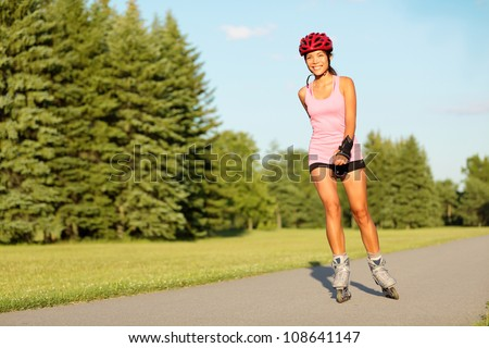 Roller skating girl in park rollerblading on inline skates. Mixed race Asian Chinese / Caucasian woman in outdoor activities.