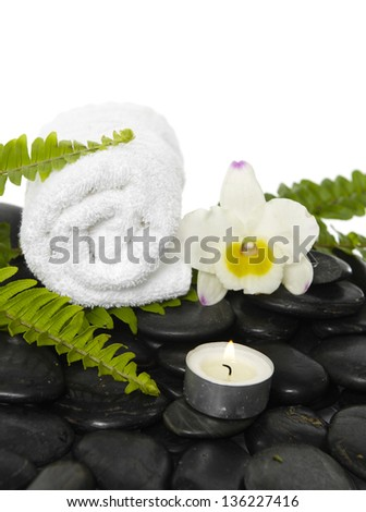 roller towel with green fern and white orchid, candle on pebbles