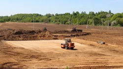 Roller tractor flattens the sand on construction site, industrial landscape design on Sunny summer day